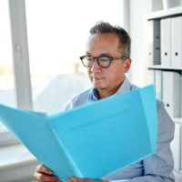 business, people and paperwork concept - businessman with folder and papers at office