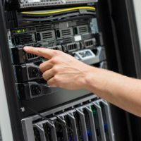 Close-up of adult male IT engineer switching on server at datacenter